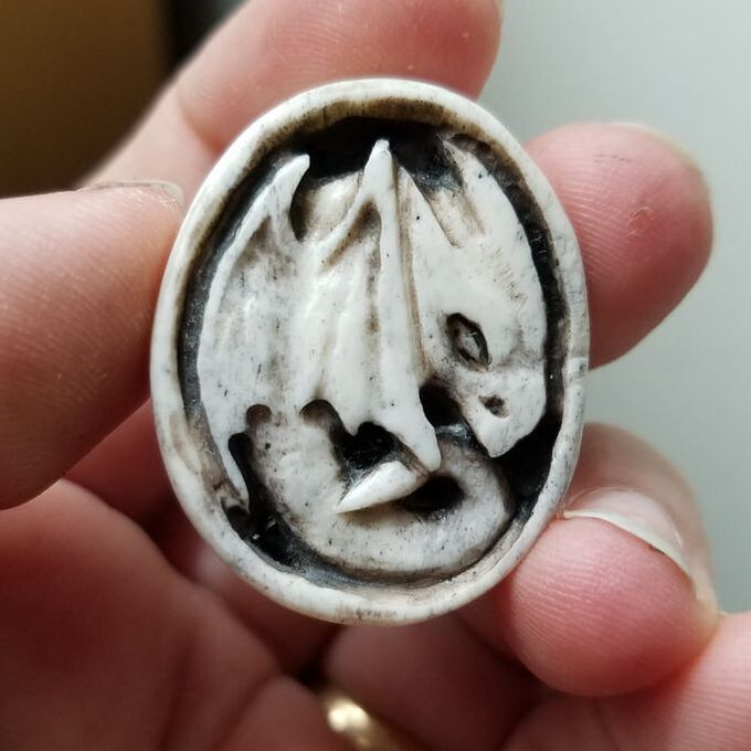 A bone cameo-style carving of a small dragon.