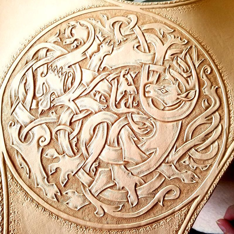 Close up of tooled Celtic stag and wolf.